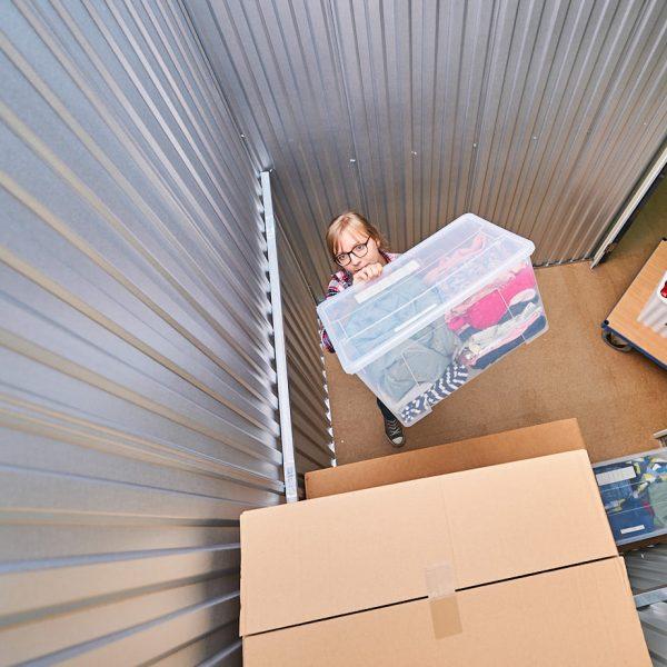 Frau stapelt Haushaltswaren im Lagerraum